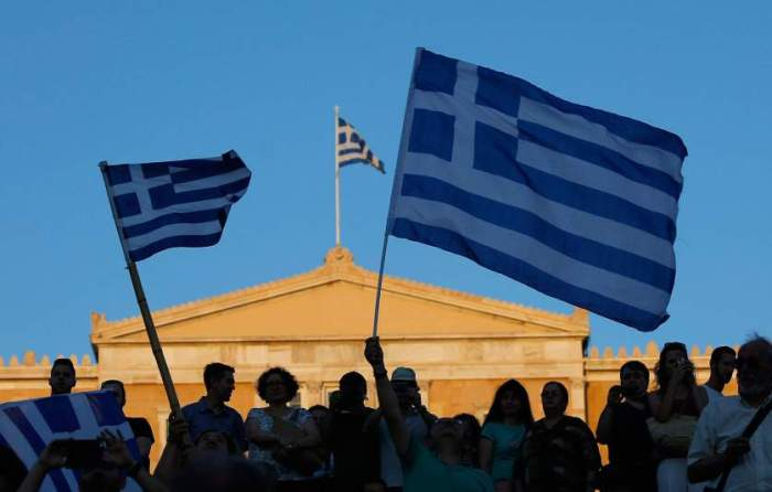 "Supporters of the No vote wave Greek flags after the referendum's exit polls at Syntagma square in Athens, Sunday, July 5, 2015. Greece faced an uncharted future as officials counted the results of a referendum Sunday on whether to accept creditors' demands for more austerity in exchange for rescue loans, with three opinion polls showing a tight race with a narrow victory likely for the ""no"" side. (AP Photo/Emilio Morenatti)"