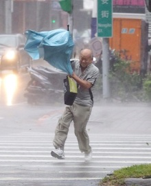 epaselect epa04954008 A man struggles with his umbrella as he crosses a street in Taipei, Taiwan, 28 September 2015 as Typhoon Dujuan slams Taiwan. Dujuan, called a strong tyhoon by the Central Weather Bureau, landed on Taiwan's east coast Monday afternoon, bringing strong wind and heavy rain and disrupting land and air traffic. Dujuan will pass Taiwan Monday night on its way to China.  EPA/DAVID CHANG BEST QUALITY AVAILABLE