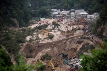 Rescue workers search for survivors after a landslide hit Cambray, a neighborhood in the suburb of Santa Catarina Pinula, about 10 miles east of Guatemala City, Friday, Oct. 2, 2015. The hill that towers over Cambray collapsed late Thursday after heavy rains, burying several houses with dirt, mud and rocks. (AP Photo/Moises Castillo)