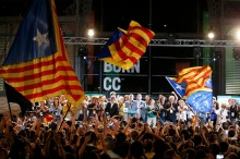 Junts Pel Si (Together For Yes) supporters wave flags while Catalan President Artur Mas and other politicians take the stage after polls closed in a regional parliamentary election in Barcelona, Spain, September 27, 2015. Separatists have won a clear majority of seats in Catalonia's parliament, an exit poll showed on Sunday, in an election that could set the region on a collision course with Spain's central government over independence.   REUTERS/Sergio Perez