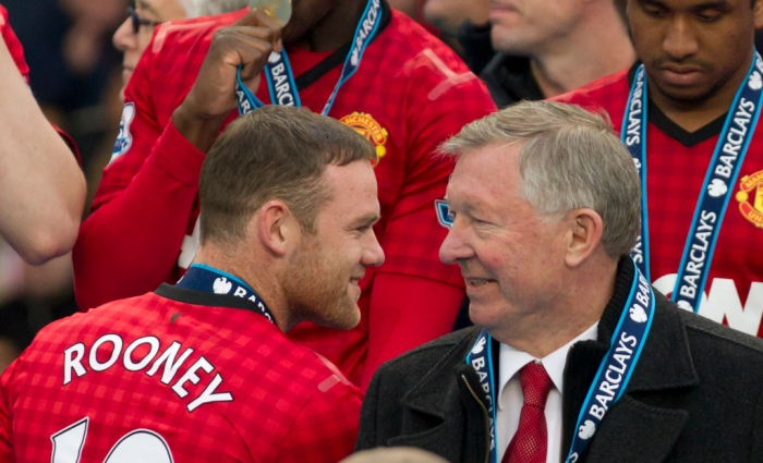 Manchester United's manager Sir Alex Ferguson, right, speaks to striker Wayne Rooney after his last home game in charge of the club, their English Premier League soccer match against Swansea, at Old Trafford Stadium, Manchester, England, Sunday May 12, 2013. (AP Photo/Jon Super)