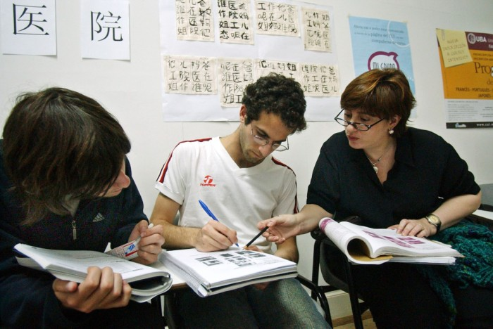Tomas Lukin, left,  Armend Derstepaniam, center, and Angeles Ascasubi attend a Chinese language class at Buenos Aires University, Oct. 18, 2005. Several hundred people who work in importing companies began studying Chinese after China's president swept through Latin America one year ago with big promises of trade deals and investments. (AP Photo/Daniel Luna)